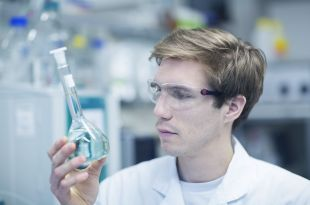 male-scientist-holding-up-and-looking-at-flask-in-lab-551984589-58a335b23df78c4758d170c8