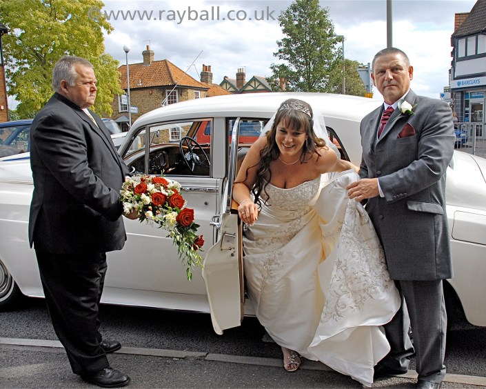 Bride struggling with dress exiting wedding car in Wandsworth..