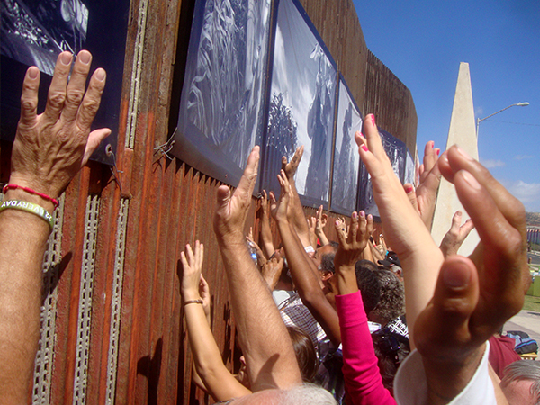 Hands raised in prayer at the border fence