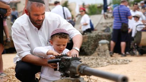 Israeli adult teaches a child how to use a gun