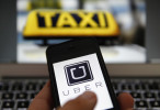 An illustration picture shows the logo of car-sharing service app Uber on a celular next to the picture of an official German taxi sign