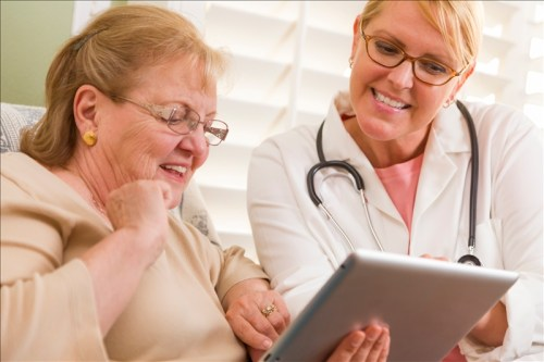 Doctor or Nurse Talking to Senior Woman with Touch Pad Computer.