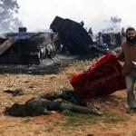 .Un hombre se dispone a cubrir con una manta el cuerpo de un sodlado pro Gadafi después de un bombardeo francés hoy en Bengasi, según señalan varios testigos.