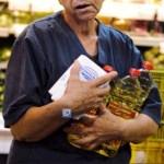 Una mujer sostiene los paquetes con botellas de aceite de azúcar y cocinar en un supermercado en Caracas. Problemas en la distribución y los controles de precios explican el faltante en los anaqueles.