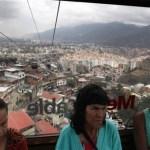 En esta foto del 14 de marzo de 2013, Marisol Lezaman, a la izquierda, Teresa Montilla, en el centro, y Yetcimar Rosales se transportan en un teleférico sobre viviendas en Caracas, Venezuela.