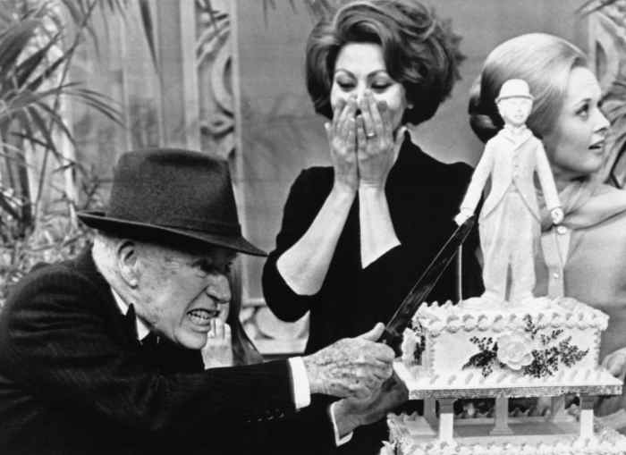Charlie Chaplin attacks his birthday cake while Sophia Loren and Tippi Hedren watch