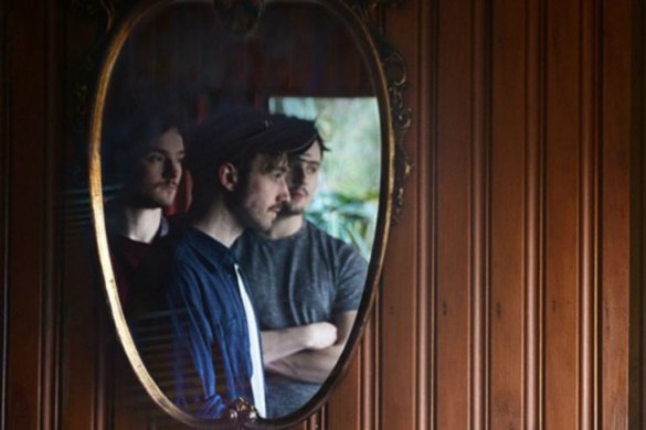 Promo image of Stillhound band reflected in a mirror hanging on a wood panelled wall