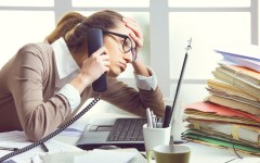 a-stressed-business-woman-looks-tired-she-answer-telephones-in-her-office-womendiseasecom