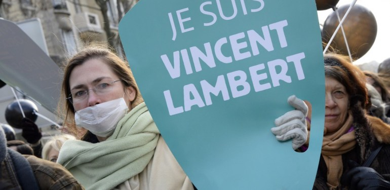 "A woman holds a placard reading ""I am Vincent Lambert"" (a quadriplegic man who is currently on artificial life support in a hospital in France) as she takes part in a walk for life ""Marche pour la vie"", on January 25, 2015, in Paris. AFP PHOTO / BERTRAND GUAY"
