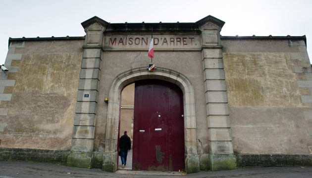 The French flag flies on October 20, 2014 at the entrance of the prison in the eastern French tow of Lure. The French Justice Ministry announced on October 15 that the Lure jail would close in 2015 due to cracks in the walls, showing that its foundations were affected by unstable ground.  AFP PHOTO / SEBASTIEN BOZON