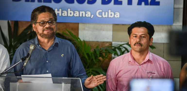 Head of leftist FARC-EP delegation in peace-talks with Colombian government, Commander Ivan Marquez (L), gives a speech next to Commander Edison Romana on April 14, 2016 in Havana. Colombian government and FARC-EP have reached deals on four of their six agenda items: justice for victims, land reform, a political role for ex-rebels and fighting the drug trafficking that fuels the conflict. The unresolved issues are disarmament and how to ratify the final accord. / AFP PHOTO / ADALBERTO ROQUE