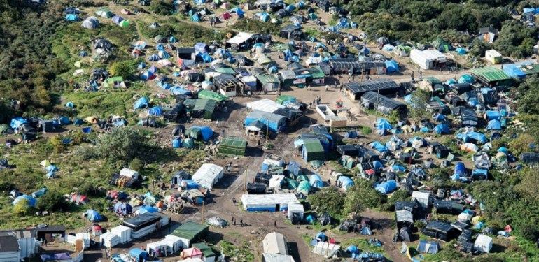 """An aerial picture taken  in Calais on October 9, 2015 shows a site dubbed the """"New Jungle"""", where some 3,000 people have set up camp -- most seeking desperately to get to England, . The slum-like migrant camp sprung up after the closure of notorious Red Cross camp Sangatte in 2002, which had become overcrowded and prone to violent riots. However migrants and refugees have kept coming and the """"New Jungle"""" has swelled along with the numbers of those making  often deadly attempts to smuggle themselves across the Channel.  AFP PHOTO / DENIS CHARLET"""