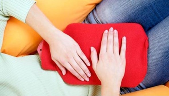 MODEL RELEASED. Menstrual pain. Woman holding a hot water bottle against her abdomen to soothe menstrual cramps.
