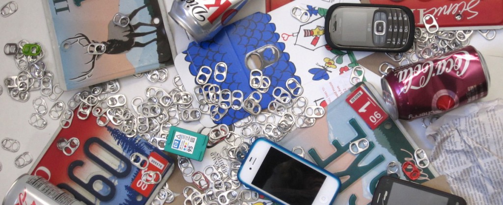 An array of recyclable items such as cans, pull tabs, phones, cardboard, newspaper