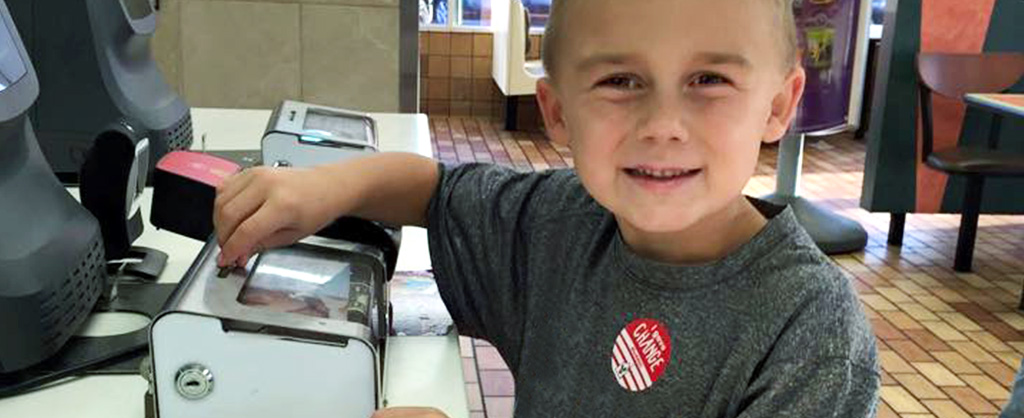 Boy Putting Coins in Donation Box at McDonald's