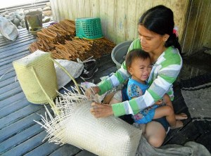Dayak villager weaving with cinnamon quills in the background