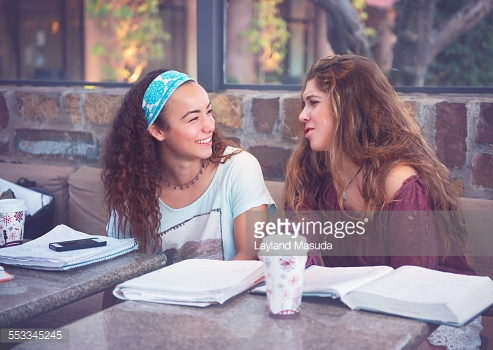 Two high school girls talking, complaining, and laughing at on outdoor cafe while doing homework together.