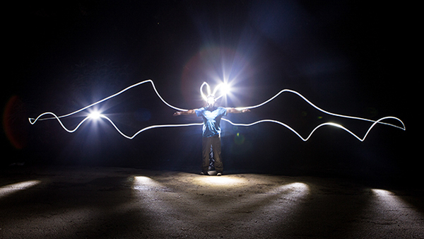 """The ROM's very own 'Batman', Assistant Curator of Mammalogy, Dr. Burton Lim with """"bat wings"""" outlined with light in a long exposure photo. Credit: Vincent Luk"""