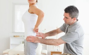 Chiropractor examining a charming woman's back