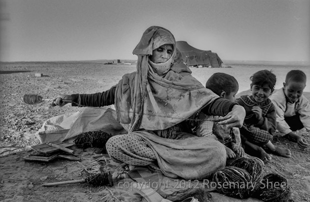 A nomad woman in Morocco sits in the desert with her children and spins