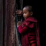 a boy monk stands in an oval doorway of Shwe Yaunghwe Kyaung