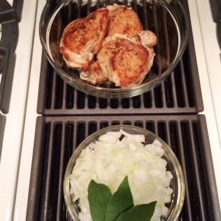 Organic chicken thighs, chopped onions and bay leaves.