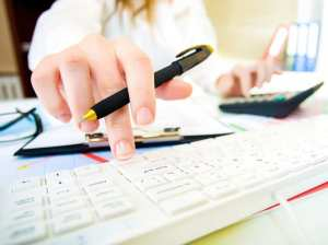 Woman with beautiful hands working on the calculator and keyboard in business office