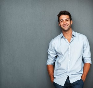 Image of man in a button down shirt leaning against a wall talking about men's skin care