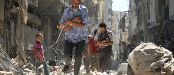 AFP PICTURES OF THE YEAR 2016 Syrian men carrying babies make their way through the rubble of destroyed buildings following a reported air strike on the rebel-held Salihin neighbourhood of the northern city of Aleppo, on September 11, 2016. Air strikes have killed dozens in rebel-held parts of Syria as the opposition considers whether to join a US-Russia truce deal due to take effect on September 12. / AFP PHOTO / AMEER ALHALBI