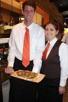 Waiters Steven Temple and Lauren Andreini present a flat bread fresh from the oven. Photo by Andrea Swayne