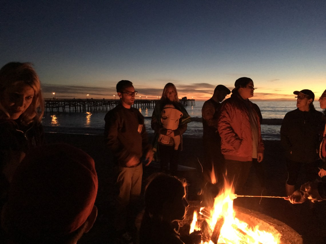 People gathered around a fire pit on Friday, Jan. 6, following a beach cleanup hosted by the San Clemente Beach Conservation Program.