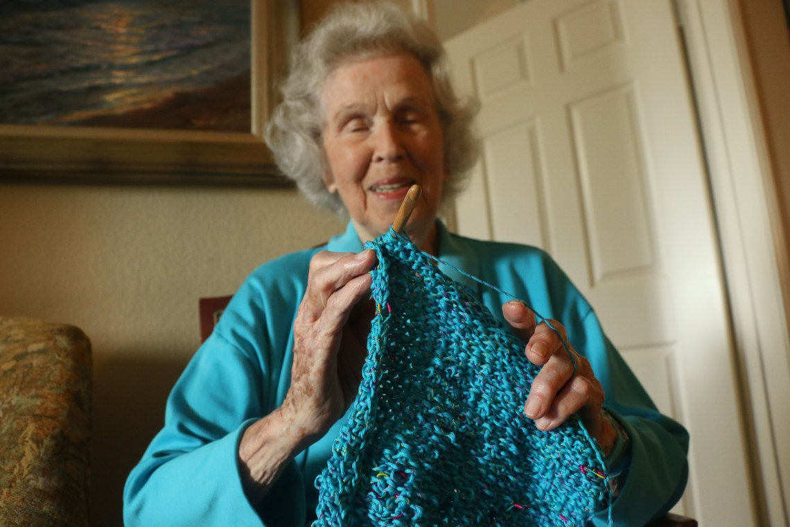 Jessie Strike-McClelland, a World War II veteran with the Australian Air Force, knits an article of clothing for children at Camp Pendleton. Photo: Eric Heinz