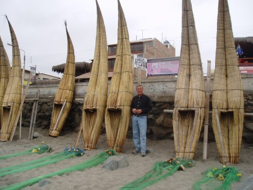 Author Joel Smith stands next to reed crafts, boats developed in ancient civilization that are still used by fishermen to navigate the surf in Huanchaco, Peru. Photo: Courtesy of Joel Smith
