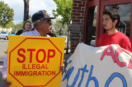 Two people with opposing views on immigration stand-off in downtown San Juan. Photo: File