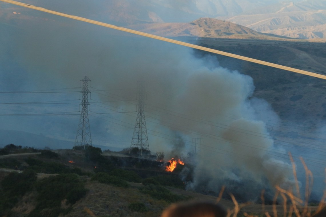 Fire on Camp Pendleton property is seen closing in on power lines on Wednesday, June 28. OCFA officials said SDG&E will monitor them to make sure they don't become a threat. Photo: Eric Heinz