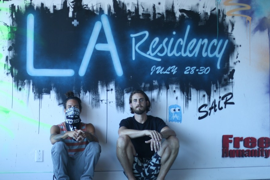 Street artist Bandit and co-chair of the Street Artist in Residence program Josh Host poses in front of the label for the LA Residency exhibit painting at the House of Trestles. The display of Los Angeles-based street art will be open to the public July 28-30. Photo: Eric Heinz