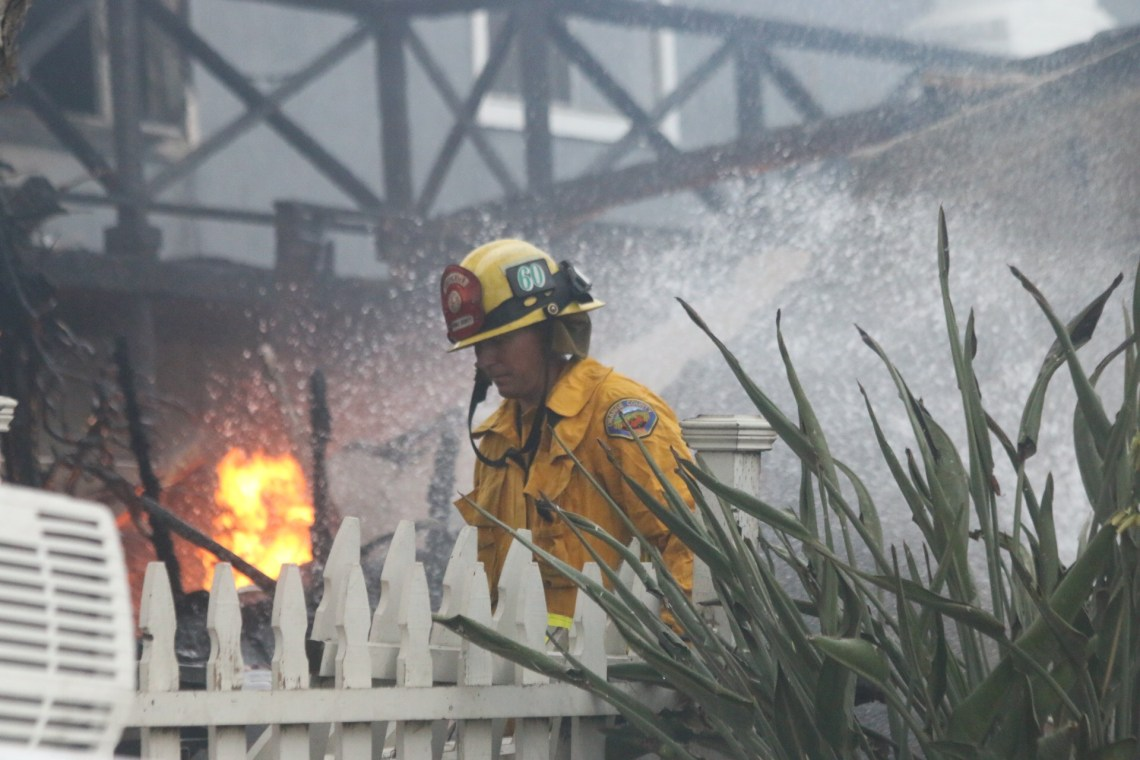 Orange County Fire Authority firefighters douse the flames of an explosion caused by a ruptured gas line on Thursday, Aug. 24, in San Clemente. Photo: Eric Heinz