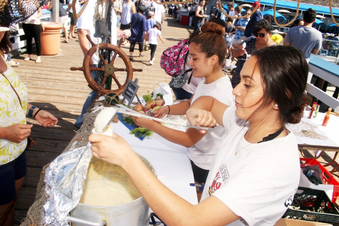 Aronid Ponce, front, and Estefani Rojas serve The Fisherman's Restaurant and Bar white clam chowder during Seafest on Oct. 1 at the San Clemente Pier.