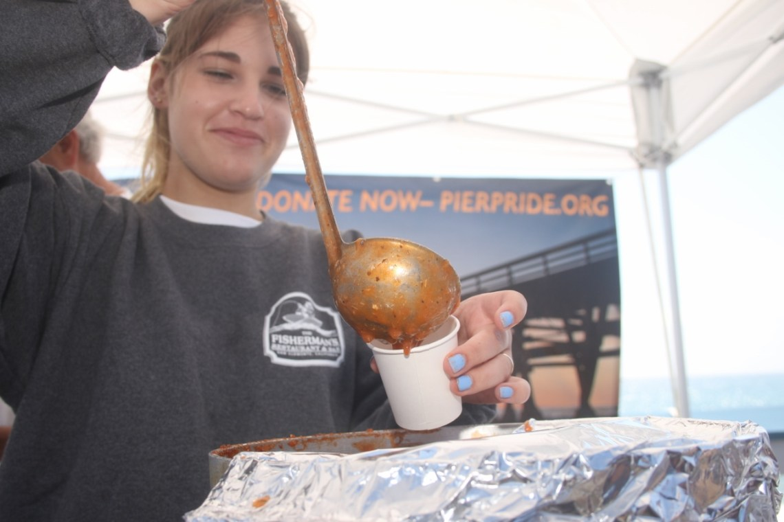Jade Steinheimer serves a red clam chowder on behalf of PierPride, which raises funds for maintenance of the San Clemente Pier.