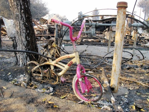 A child's bicycle rests against the remains of a subdivision in Sonoma County, where wildfires caused tens of thousands of people to evacuate last week. Photo: Jake Howard