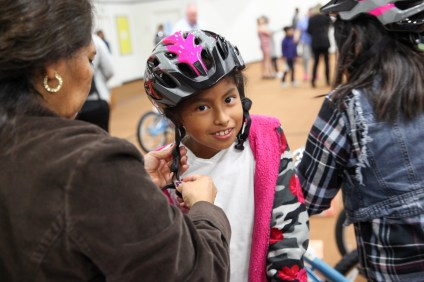 Stephanie Escobar, 9, of San Clemente, waits patiently as her mother, Virginia Barrera, adjusts her helmet.
