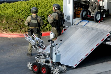 "OCSD Bomb Squad personnel bring out a bomb-defusing robot during an incident Monday, Dec. 18, in which a man barricaded himself inside a unit and claimed to have ""explosives."" Photo: Eric Heinz"