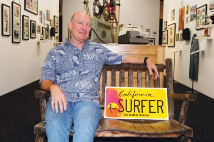 SHACC Executive Director Glenn Brumage sits in Bruce Brown's favorite chair, taken from his house in Central California where it overlooked the ocean, with a prototype of the soon-to-be-available 'The Endless Summer' special-interest license plate. Photo: Daniel Ritz