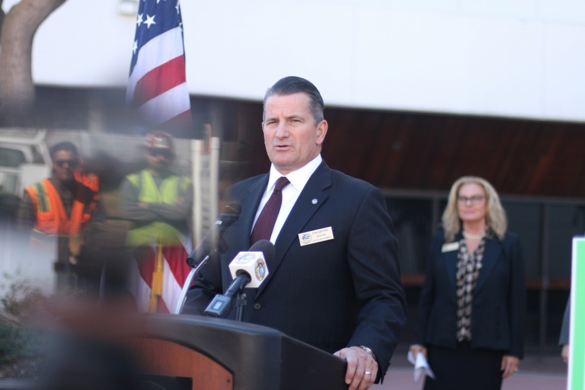 Mayor Tim Brown speaks at a press conference about the city's traffic alleviation study that was introduced on Thursday, March 1 in Santa Ana. Two construction workers who paused for the speeches are reflected in a cellphone. Photo: Eric Heinz