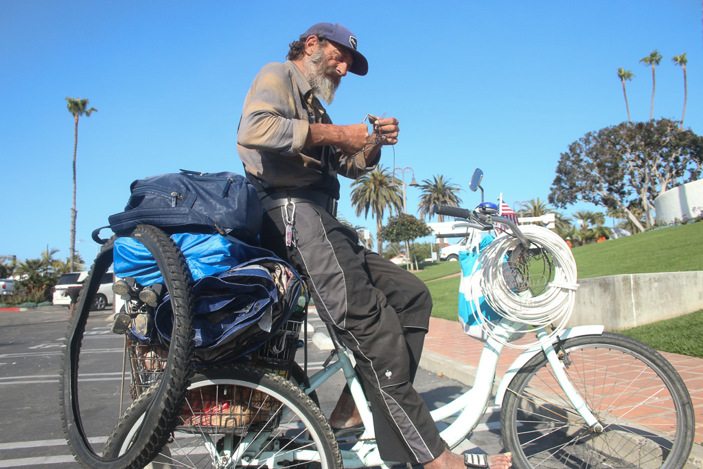 "Nick, a homeless man who lives in San Clemente, sits atop his bicycle on April 9 near the Ole Hanson Beach Club. Nick, who didn't give his last name, said he's been in San Clemente for six months. He said he's had to deal with prejudice and harassment from people who ""blame everything on us."" Photo: Eric Heinz"