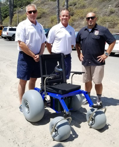 Members of the San Clemente Elks Lodge and Marine Safety Division gathered on Monday, July 30, as the Elks donated another electric wheelchair to the lifeguards. Photo: Courtesy of the San Clemente Elks Lodge
