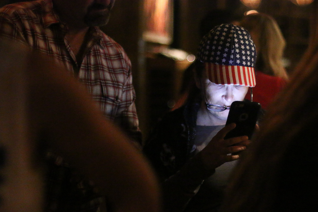 Martina McBurney-Wheeler checks her phone for election results updates during an election night party for Dan Bane and Gene W. James. Photo: Eric Heinz