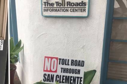 "A ""No Toll Road through San Clemente"" sign is propped up in a planter in an undated photo near The Toll Roads customer service center in San Clemente. Photo: Screenshot sourced from Ulnick Group blog"