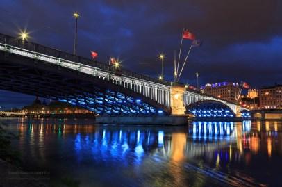 Illuminated bridge over the Rhone river at dusk.