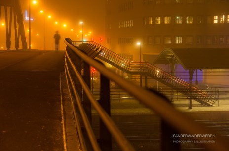 Commuter walking on a bridge above a trainstation.